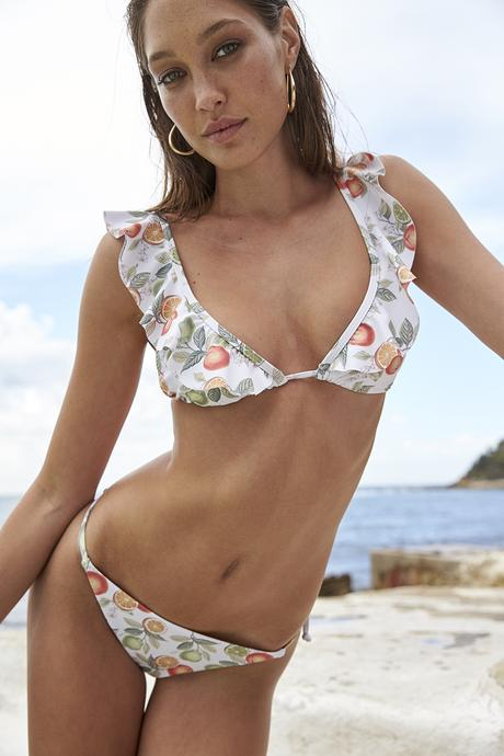 Model wears a minkpink bikini bottom. The Valencia fixed string bottoms have citrus fruits all over them but the base of the bikini is white.