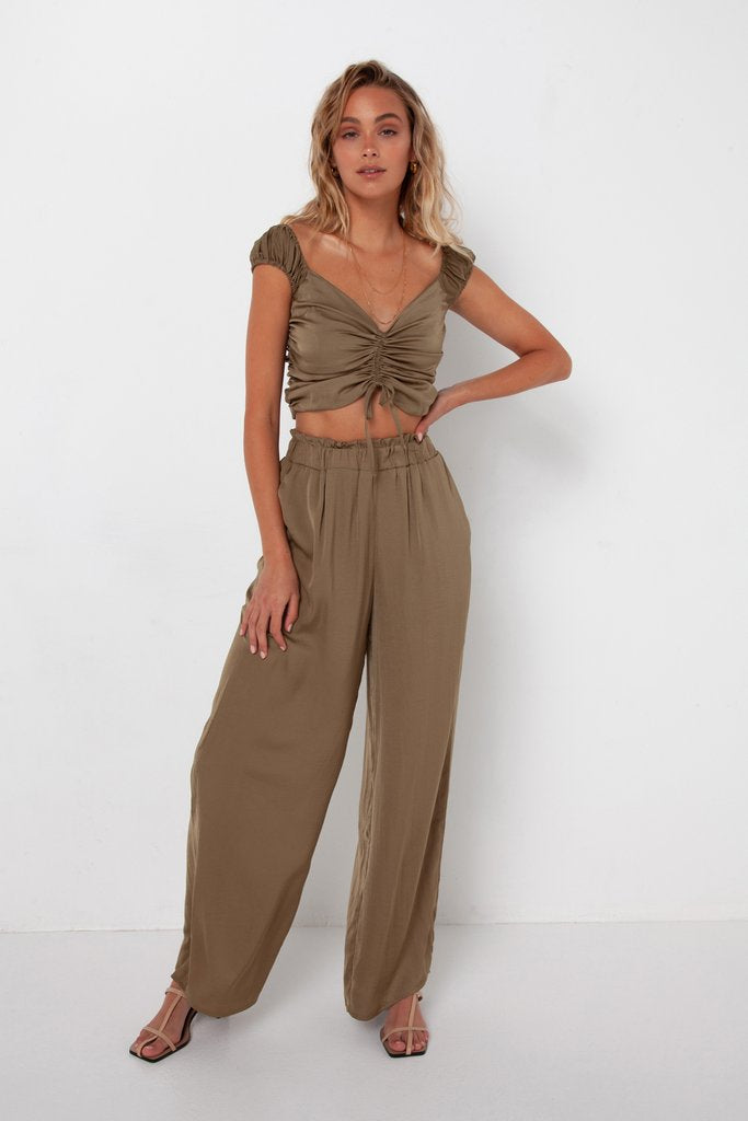 UNIKONCEPT LIFESTYLE BOUTIQUE: The model is wearing the Natasha pant in the olive colour by Madison The Label. This pant is a relaxed wide leg style that has an elasticized paper bag waist. These pants have side pockets.