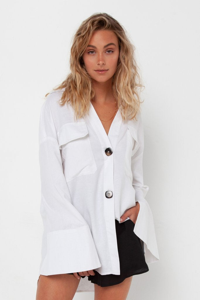UNIKONCEPT LIFESTYLE BOUTIQUE: This model is wearing the Amine shirt by Madison the Label in the colour white. The top is an oversized fit and has a chelsea collar with two large functional pockets along the bust. It features two functional tortoise buttons and oversized long sleeves that flare out.
