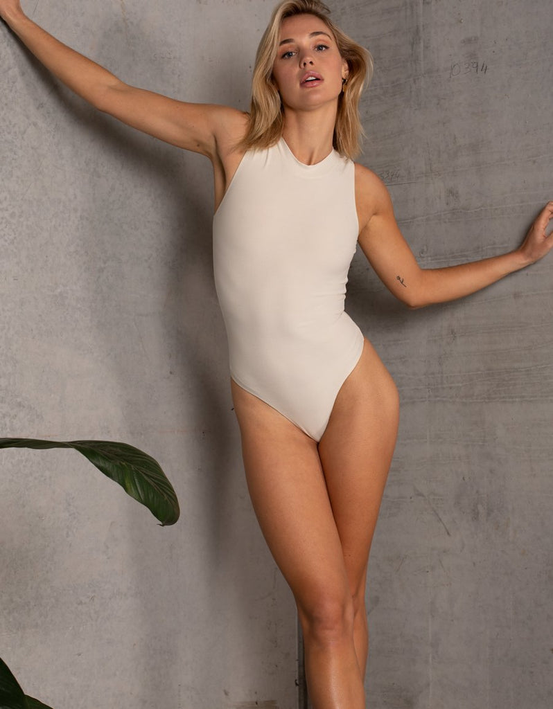 UNIKONCEPT LIFESTYLE BOUTIQUE: This model is wearing the Melbourne Bodysuit by Dream Bandits in the colour cream. The bodysuit has a high mock neckline and is sleeveless with a high cut brief, including 3 crotch clippers for various sizing and comfortability.