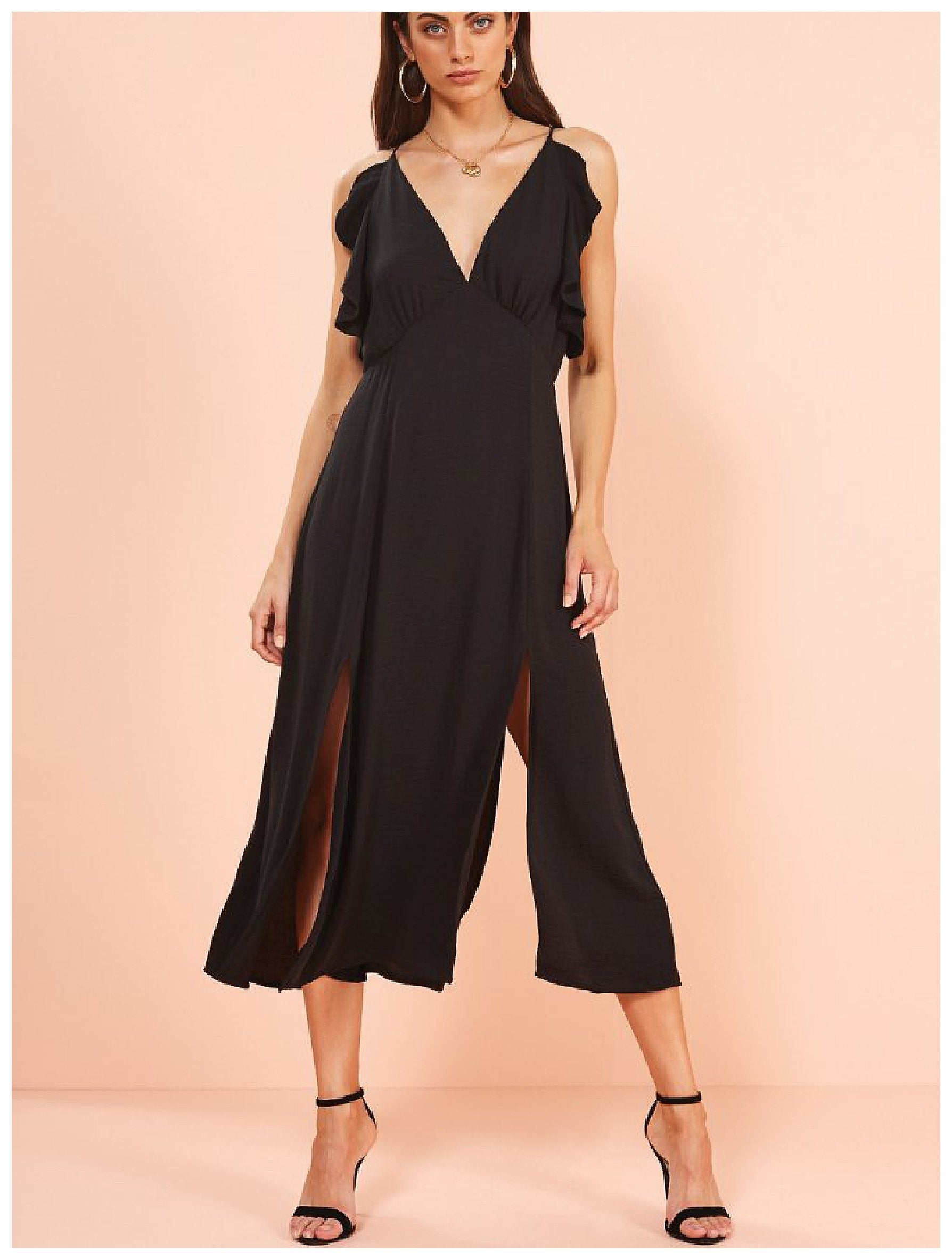 Model wears a MinkPink dress. The Vera Maxi Dress is a black chiffon-like midi dress with ruffles along the side of the breast, the dress has a v shaped neckline and two slits on either leg with an open back.