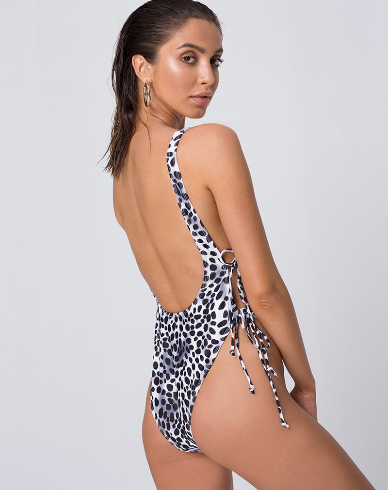 Back view of a model wearing a high cut, black and white Dalmatian print one-piece swimsuit. It features a low, scoop back, cheeky cut and open sides with adjustable side ties.