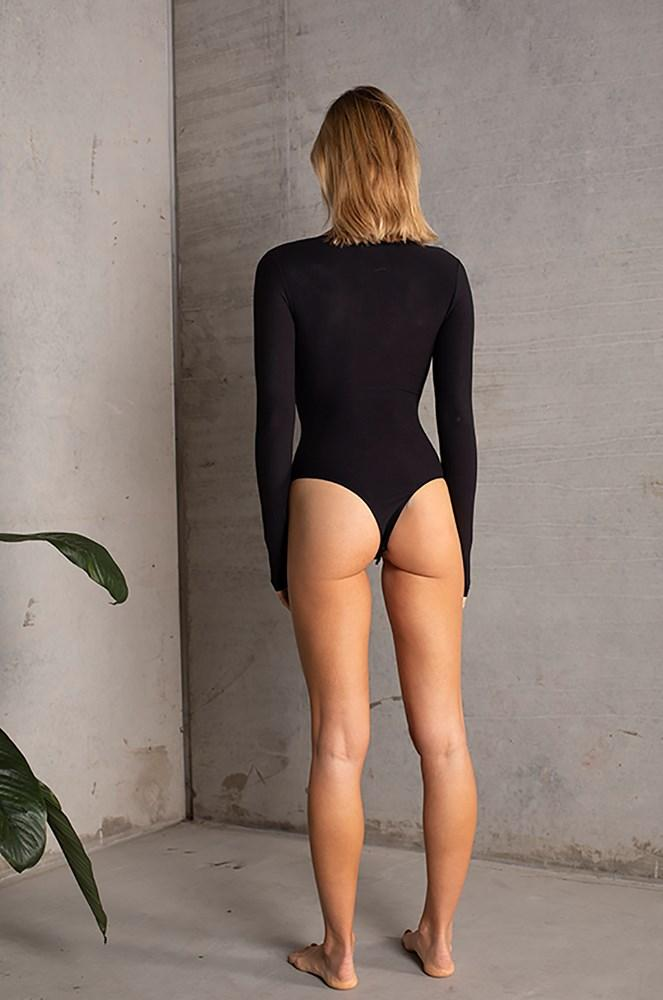 UNIKONCEPT LIFESTYLE BOUTIQUE: This model is wearing the Paris Bodysuit by Dream Bandits in the colour black. The bodysuit is long sleeve and it features a snap button detail across the neckline, and it can be closed up or undone to convert to a splice neckline detail.