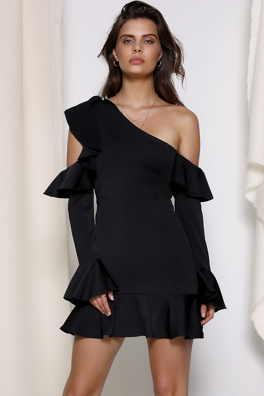 Model is wearing the Jackie Ruffle dress in black from Prem. The Jackie ruffle dress features a cutout at the shoulder on one full length arm and ruffle along the neckline. The dress is structured and has a gold zipper at the back.
