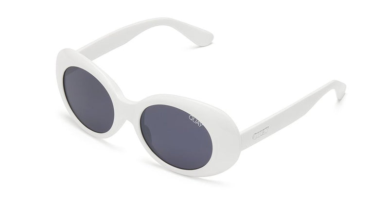 Image shows an Oval shaped Quay sunglass. The Frivolous sunglass comes with white frames and smoke lenses.