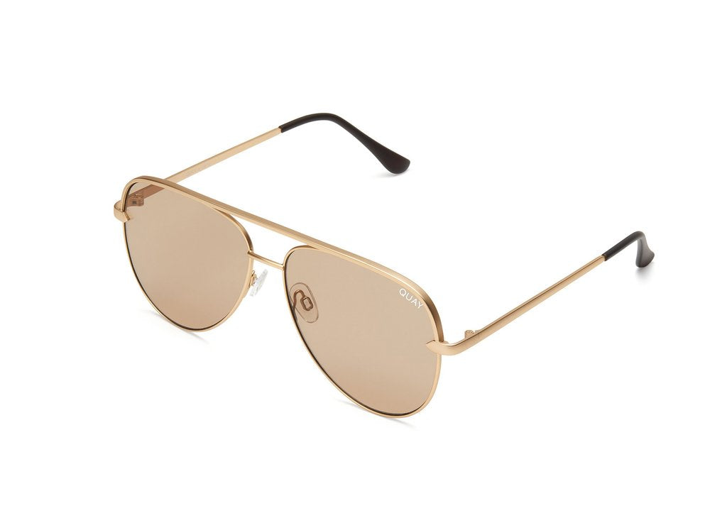 Image shows a pair of Quay Australia sunglasses. The Sahara sunglass by Desi Perkins features Matte Gold framed aviators with gold gradation on the lens.