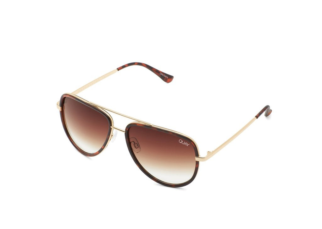 UNIKONCEPT: Lifestyle boutique; Image shows an aviator styled sunglass by Quay. The All in sunglass by Quay is in the colour tortoise shell colour and a brown fade. It has a gold bridge over top on the nose.