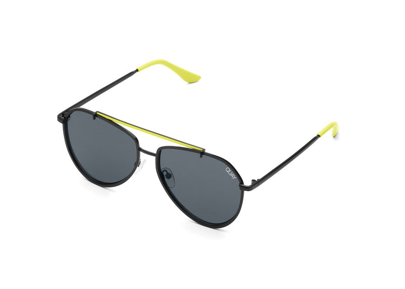 UNIKONCEPT: Lifestyle boutique; image shows a pair of Quay sunglasses. The dirty habit sunglass is an aviator style with full black frames, it does features a bright yellow bridge over top of the nose and stems of the side handles.