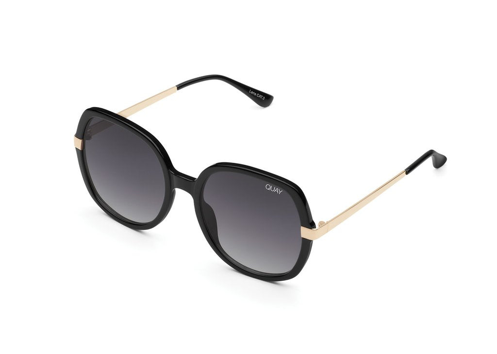 UNIKONCEPT: Lifestyle boutique; image shows a pair of quay sunglasses. The Gold dust sunglasses are a large, oversized circular/square like frames with small gold detailing around the outer eyes.