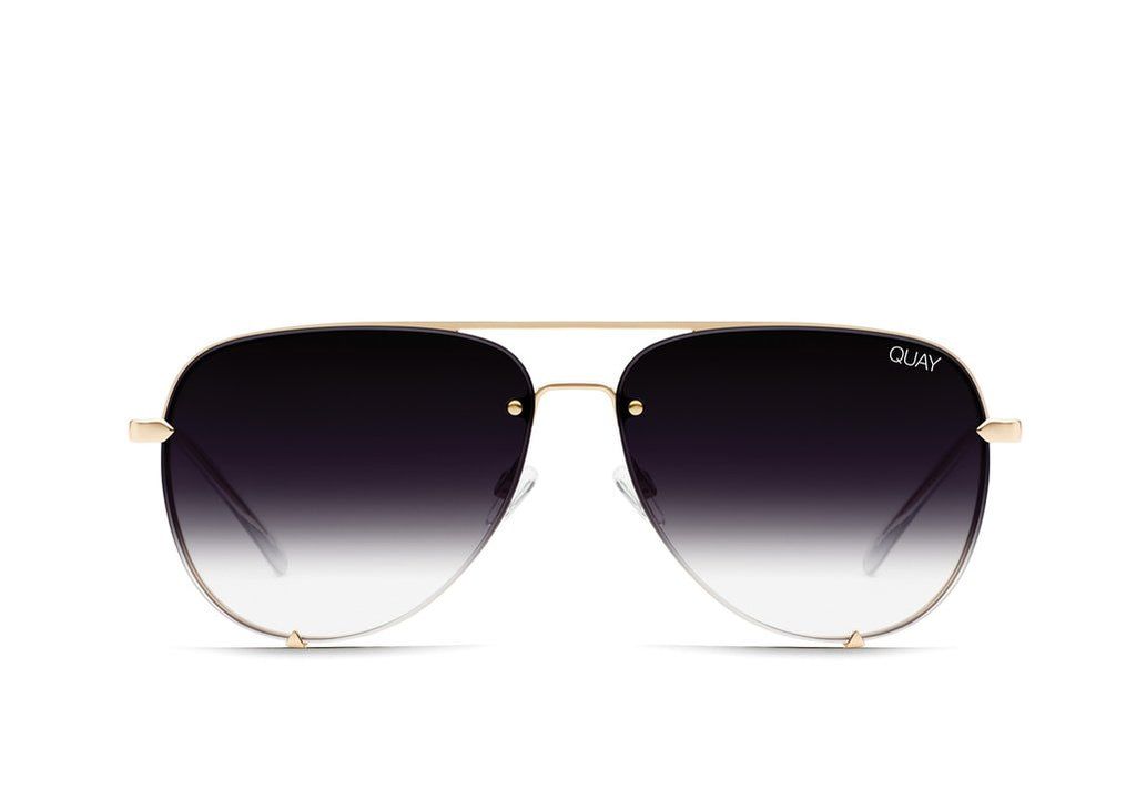 Image shows a pair of Quay Australia sunglasses. The high key mini is an aviator styled sunglass with no rims. It has gold arms and bridge between the eyes and comes with a faded dark smoke to light grey lens.