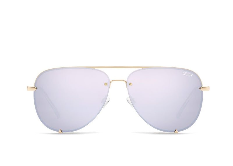 Image shows a pair of Quay Australia sunglasses. The high key lilac rimless sunnies are an aviator style with gold arms and bridge as well as small gold triangles are featured at the bottom of the glass. They are lilac in colour.