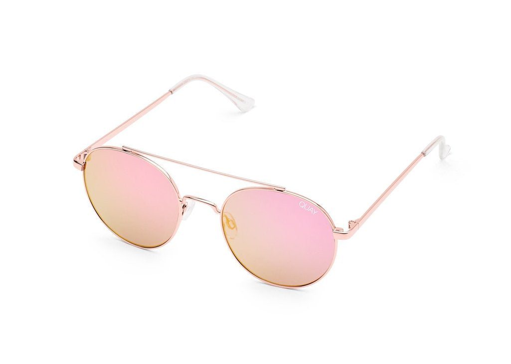 Image shows a pair of black circular Quay Australia sunglasses. The outshine sunnies are gold and have a large bridge connecting the two shades, the lenses are a pink colour.