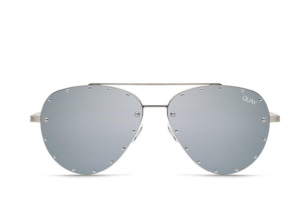 Image shows a pair of Quay Australia sunglasses. The Roxanne sunglass by Jaclyn Hill are silver framed aviators with a dark grey lens. The sunglass features small studs around the exterior of the glass.