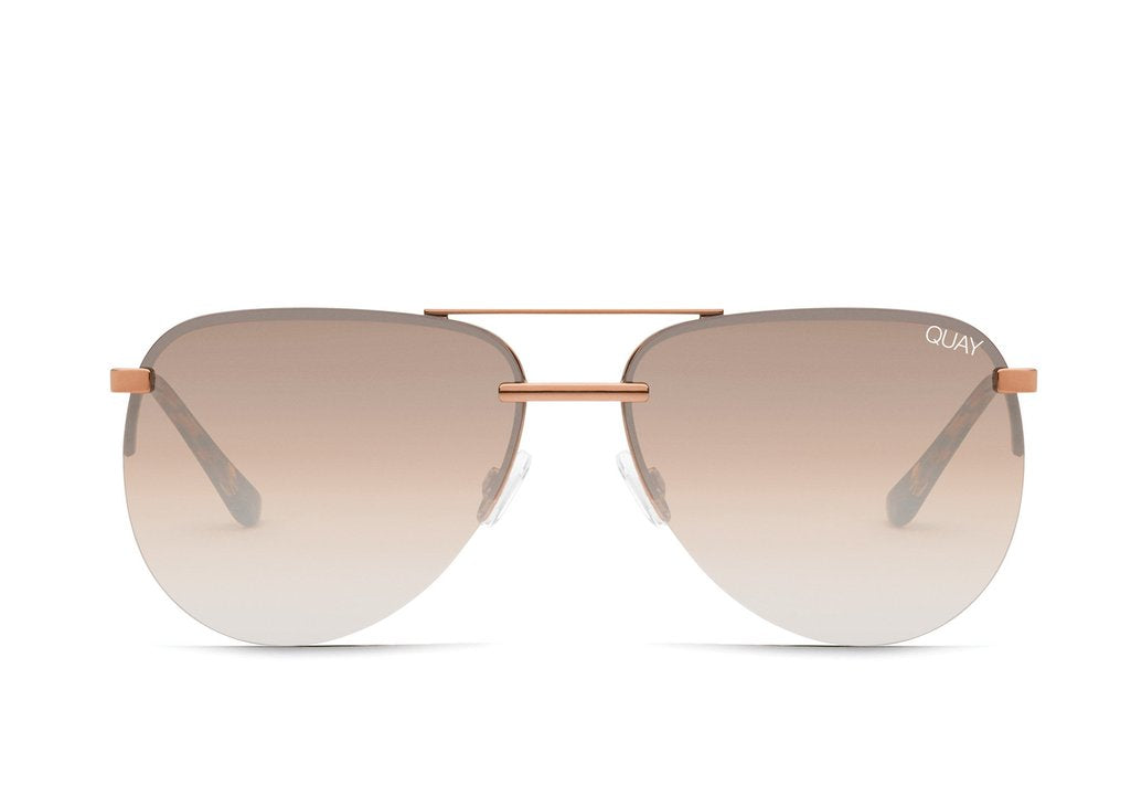 Image shows a pair of Quay Australia sunglasses. The playa sunglass created my Jennifer Lopez is an aviator style of sunnie with rose gold frames and bronze/brown lenses.