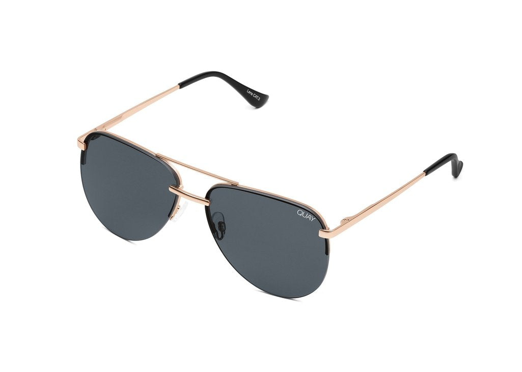 Image shows a pair of Quay Australia sunglasses. The playa sunglass created my Jennifer Lopez is an aviator style of sunnie with gold frames and black lenses.