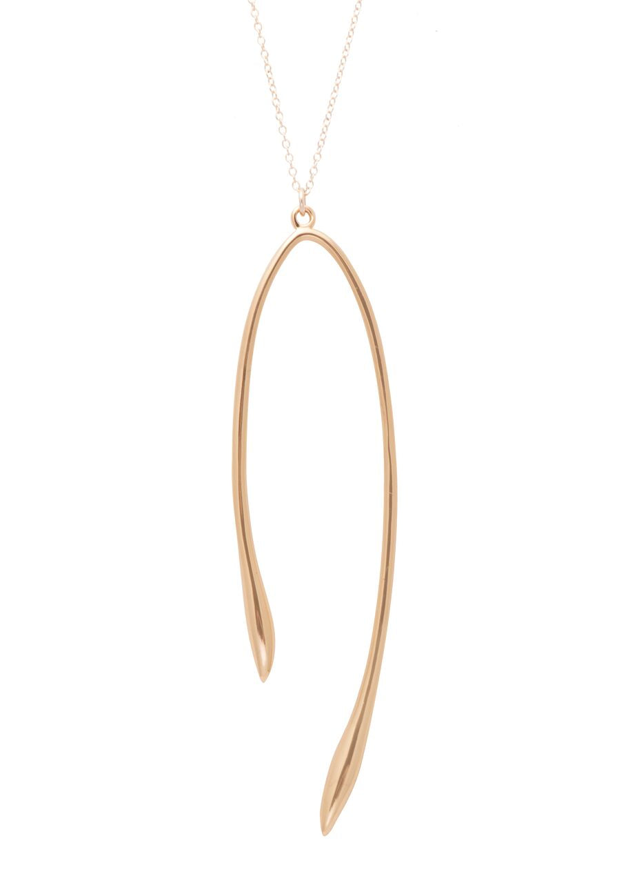 Images shows a gold Sarah mulder necklace. The Rebel necklace is a thin gold chain featuring a wishbone like pendant.