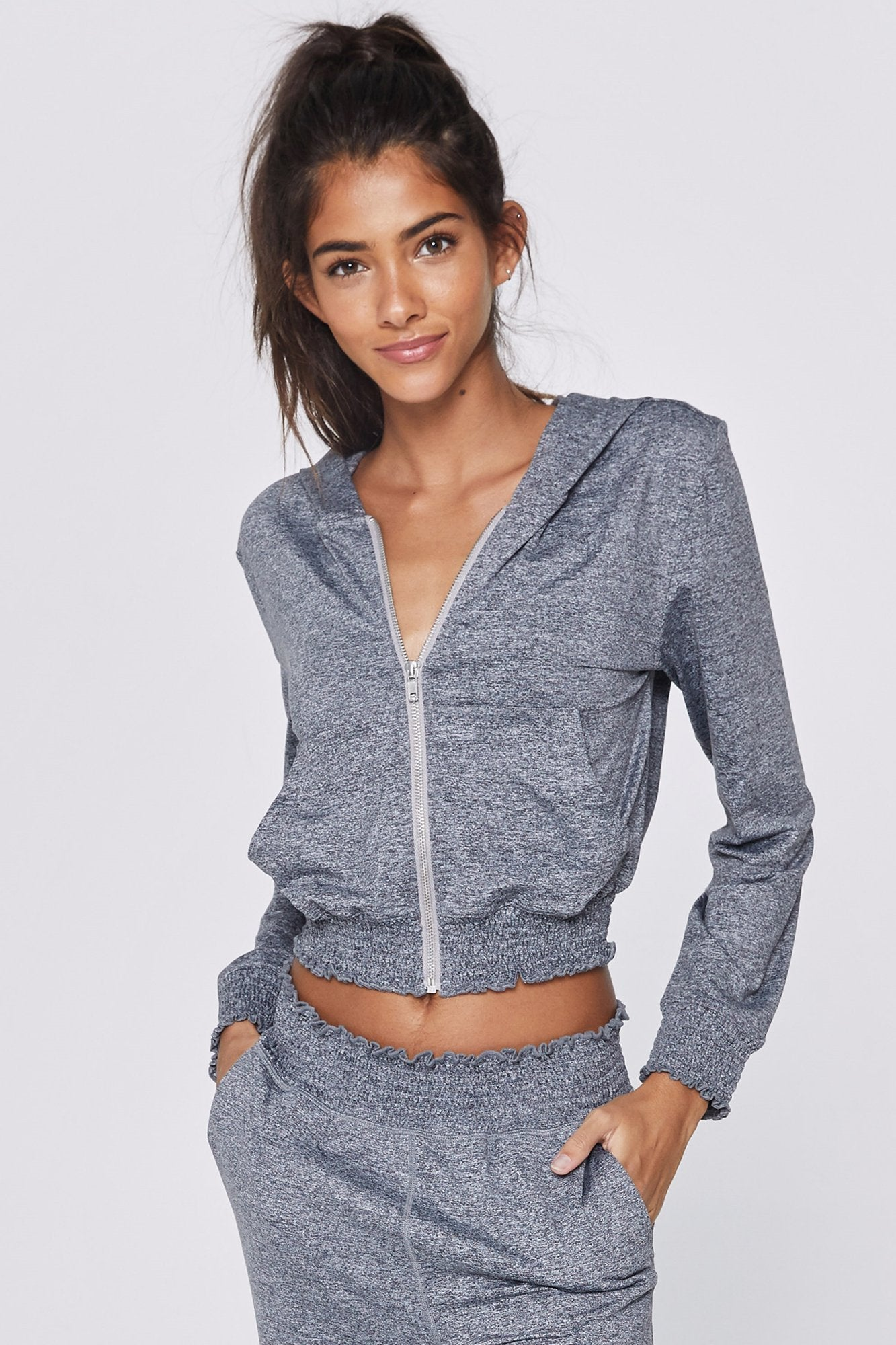 "Model is wearing heathered grey zip up hoodie that features pockets, a light grey zipper and writing across the back in dark grey that reads ""spiritual Gangster""."