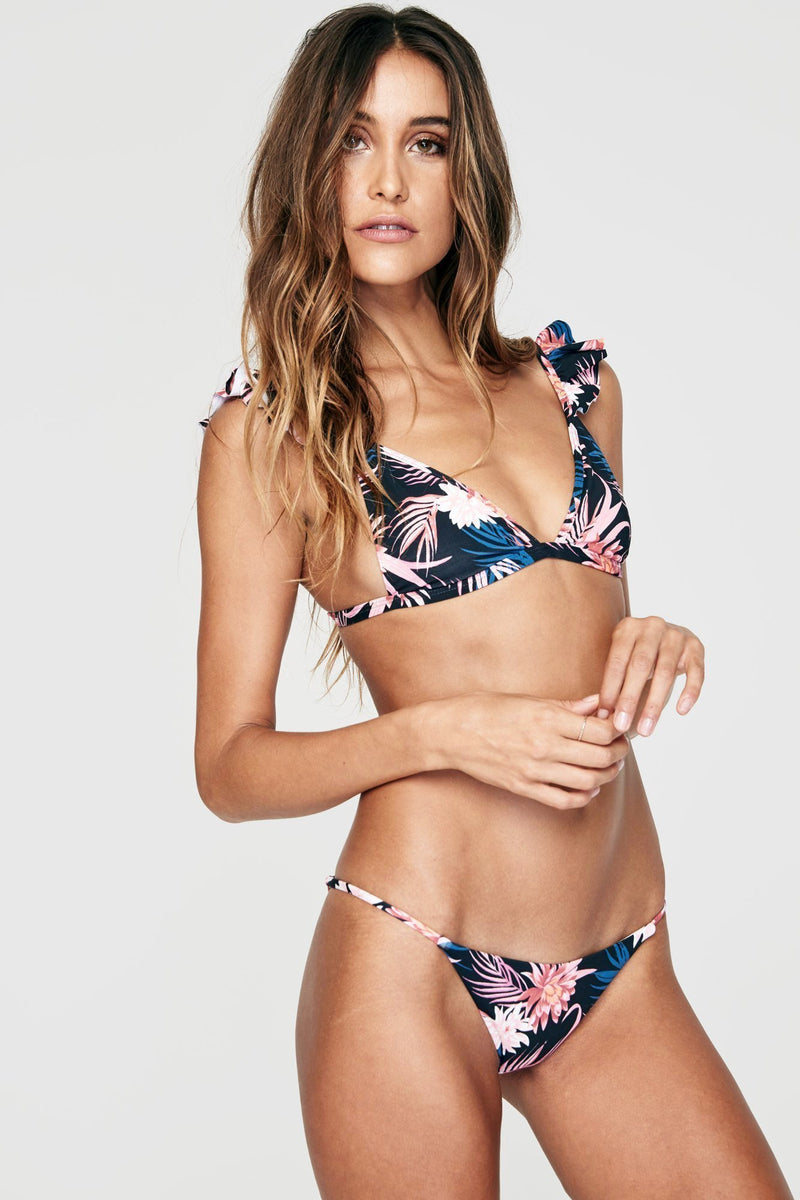 Front view of model wearing a navy and light pink spiritual gangster floral print triangle bikini top. The wanderer bikini top In the print tropics features a v-neck, and ruffles on the spaghetti straps.