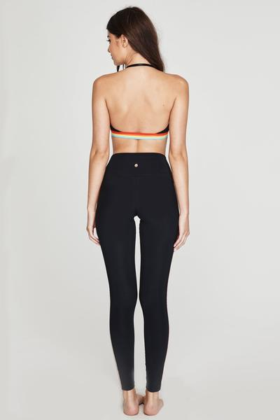 "Model wearing high waisted spiritual gangster leggings. The 7/8 high vibe legging in glossy is black. Down the right front leg, ""Spiritual Gangster"" written in black glossy lettering."