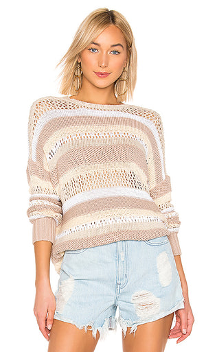 UNIKONCEPT Lifestyle boutique: Model is wearing a white, beige and dusty rose striped, knit, over-sized show me your mumu sweater. The Yala sweater in sand dune stripe is a full long sleeved oversized sweater that features horizontal stripes of knit neutral shades.