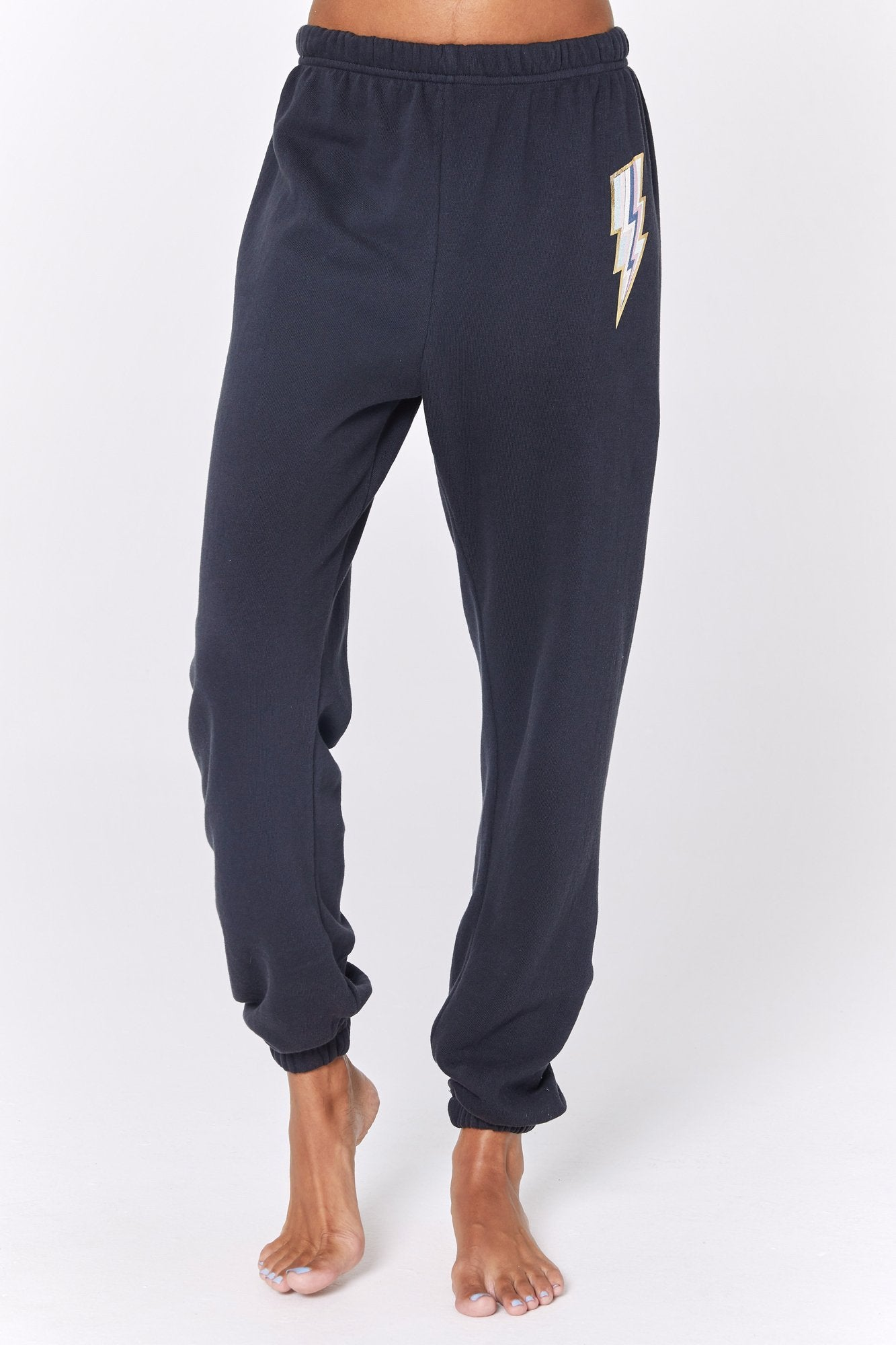 Model is wearing dark grey spiritual gangster sweatpants. The lightning lightweight sessions sweatpant has elastic bottoms and waist band. The sweatpants feature a lightning bolt on the left upper thigh outlined in white with blue and pink stripes through it.