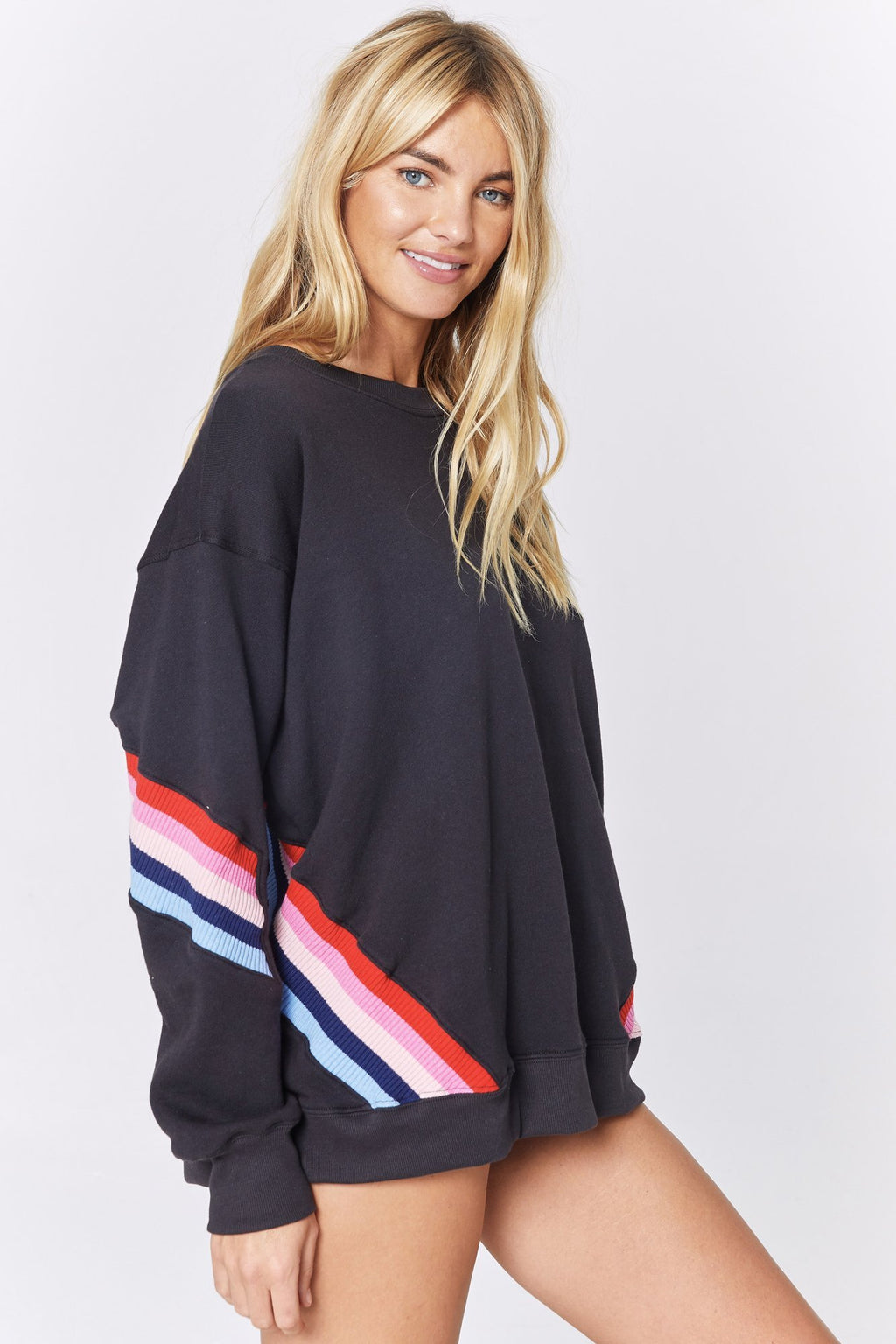 Side view of model wearing an oversized, relaxed fit ,spiritual gangster crew sweatshirt. The stripe crew neck sweatshirt in a vintage black colour with blue, pink, and red stripes placed at a 45 degree angle on both sides of the lower  body and lower sleeve.