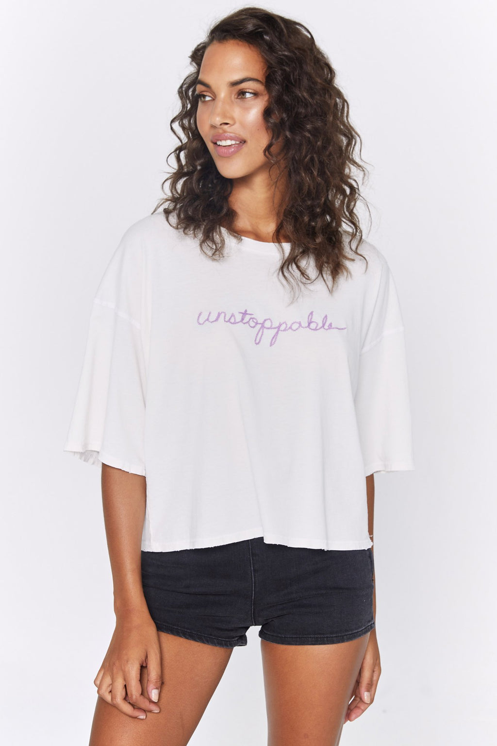 "Model wears a white over-sized spiritual gangster t-shirt. The unstoppable icon boyfriend tee has pink script that reads ""unstoppable""."