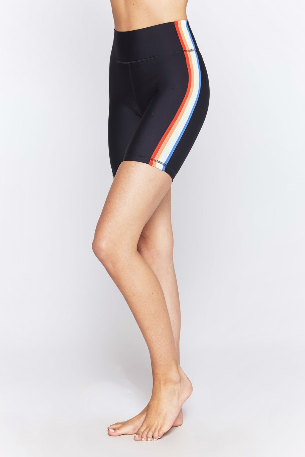 Model is wearing black athletic spiritual gangster biker shorts. The gangster biker shorts in black with a 5-colour rainbow stripe running vertically down the side seam hem on both sides.
