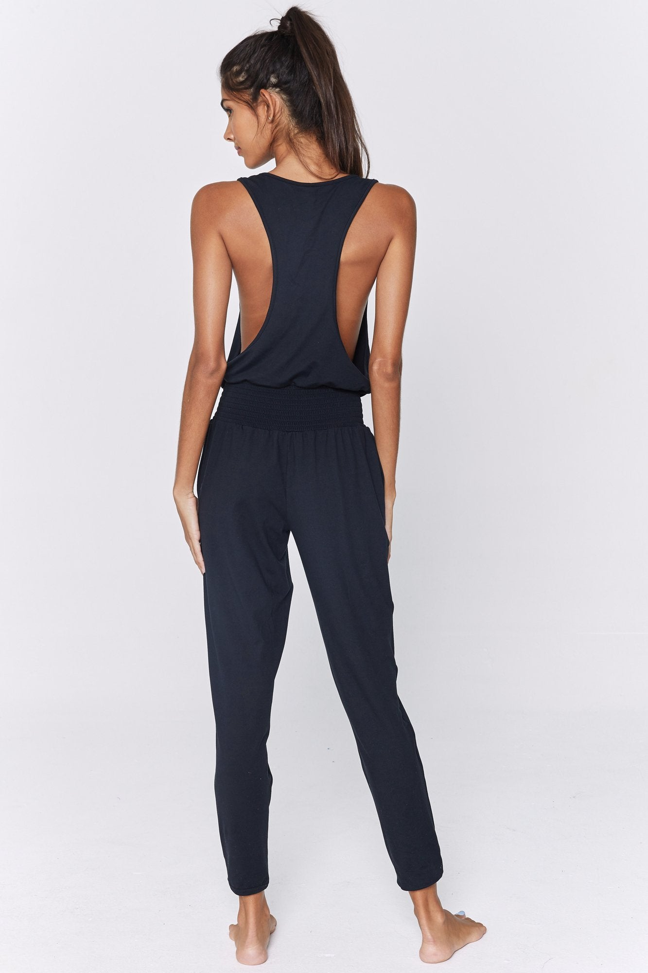 Back view of model wearing a one-piece, sleeveless jumpsuit in a black flowy and stretchy fabric. The jumpsuit features a loose-fitting racer back, side slit pockets, an elastic waist, tapered pants, and an elastic cuff around the ankle.