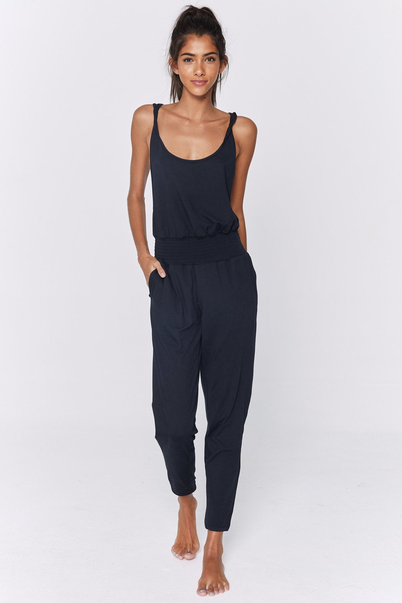 Front view of model wearing a one-piece, sleeveless jumpsuit in a black flowy and stretchy fabric. The jumpsuit features half-inch straps, a scoop neck, side slit pockets, an elastic waist, tapered pants, and an elastic cuff around the ankle.