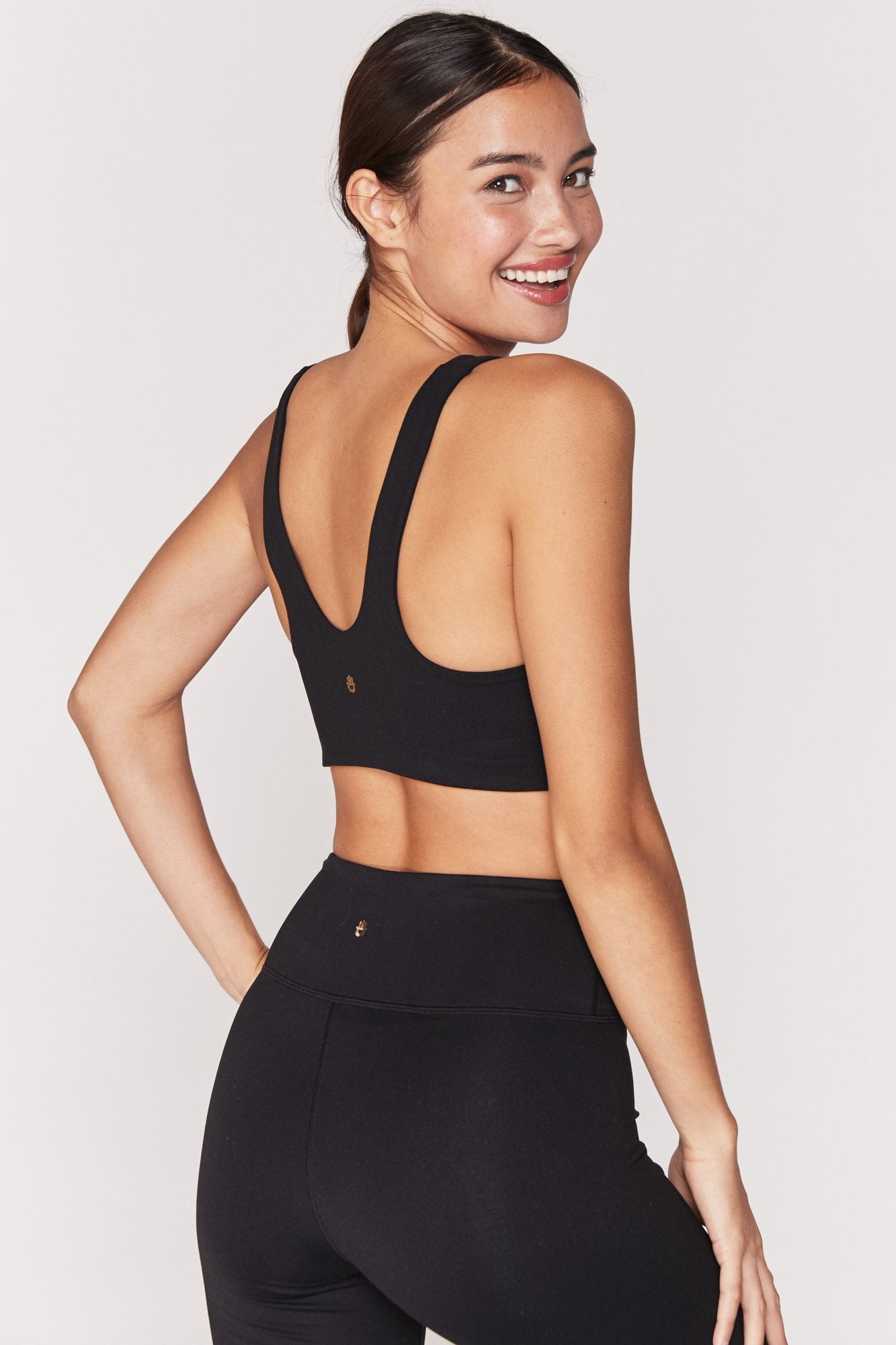 "Model is wearing black, spandex, scoop neck, spiritual gangster sports bra. The shake bra in matte black has Text across the chest reads in matte black ""Spiritual Gangster""."