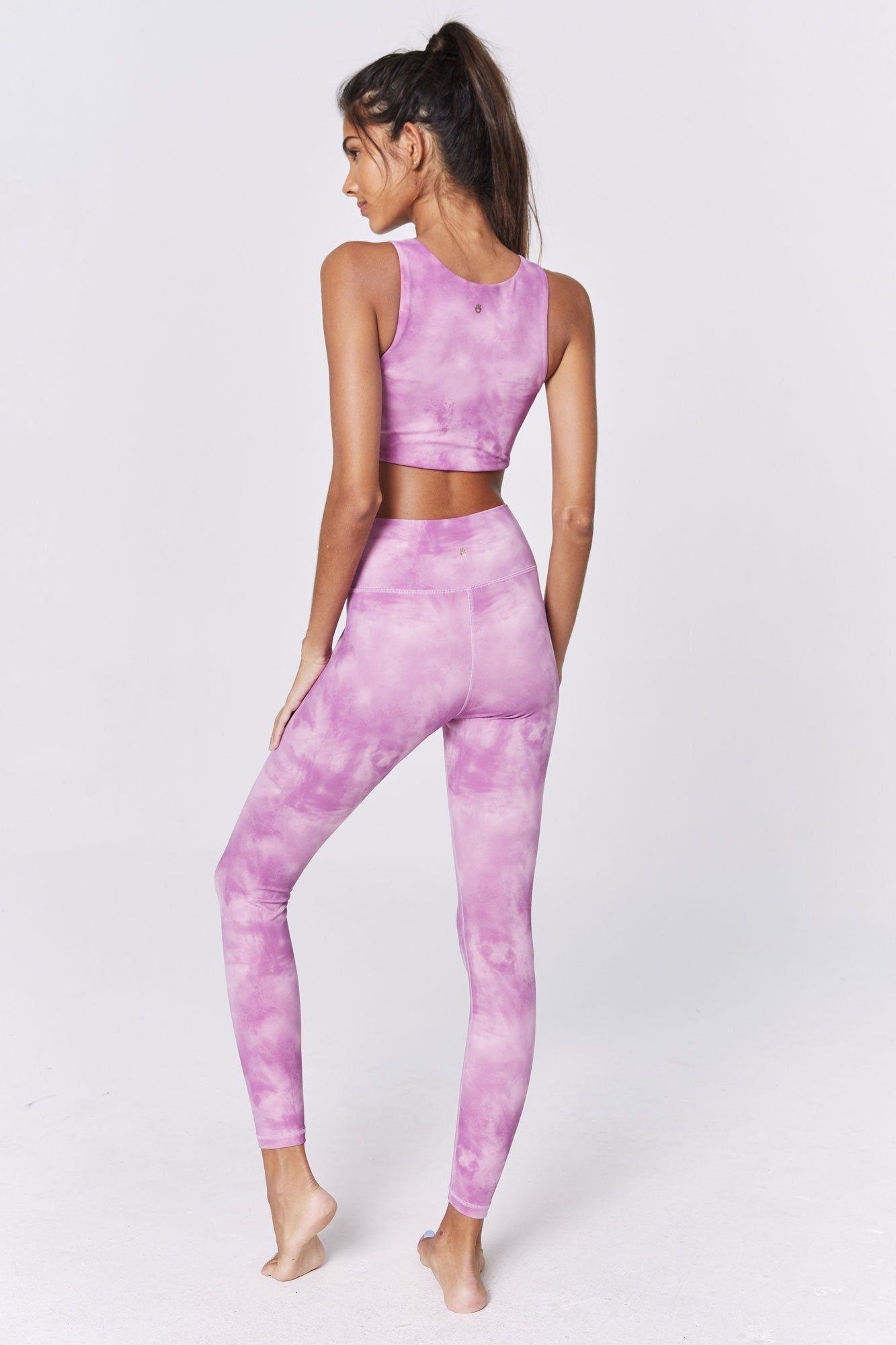 Model is wearing high-waist light and dark pink tie-dye spiritual gangster leggings. The perfect high waist 7/8 legging sunset in dye print is super high waisted and full length.