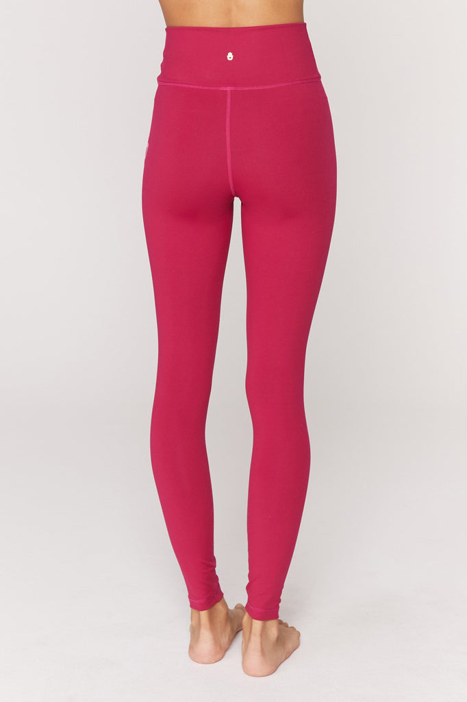 UNIKONCEPT Lifestyle boutique: Image shows the essential HW leggings by Spiritual Gangster. These highwaisted leggings come in berry red with the brand name printed down the left leg in pink capital lettering.