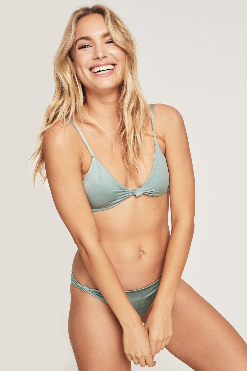 model is wearing light, dusty green spiritual gangster triangle bikini top. The Cozumel bikini top in sage features a knot detail at the centre and spaghetti straps.