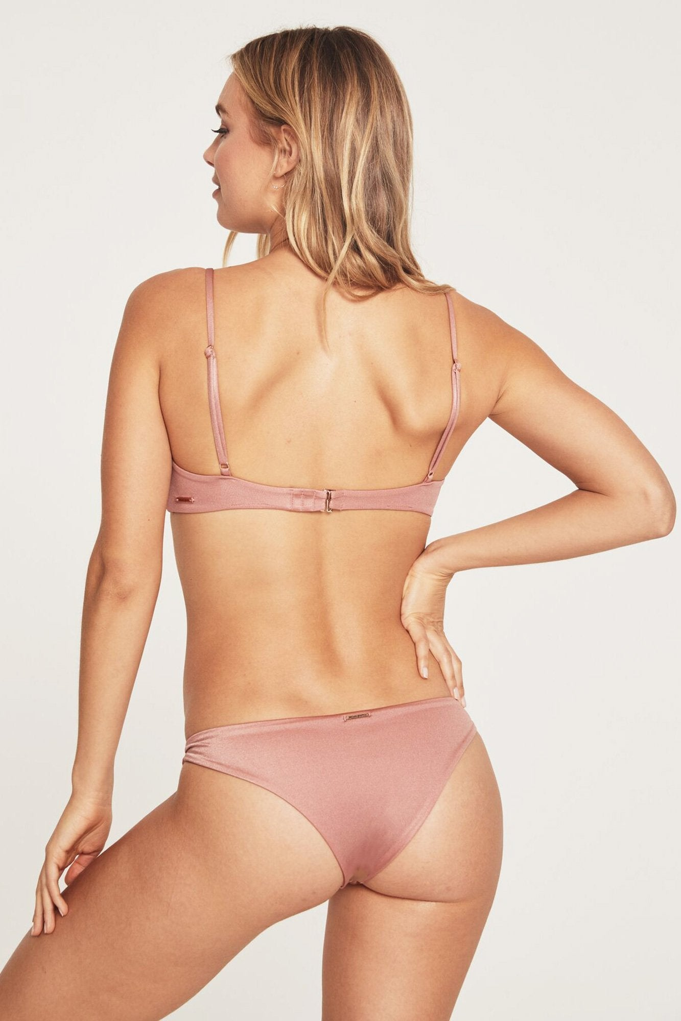 Back view of model wearing light, dusty pink low-rise bikini bottoms featuring knotted side detail and a cheeky cut.