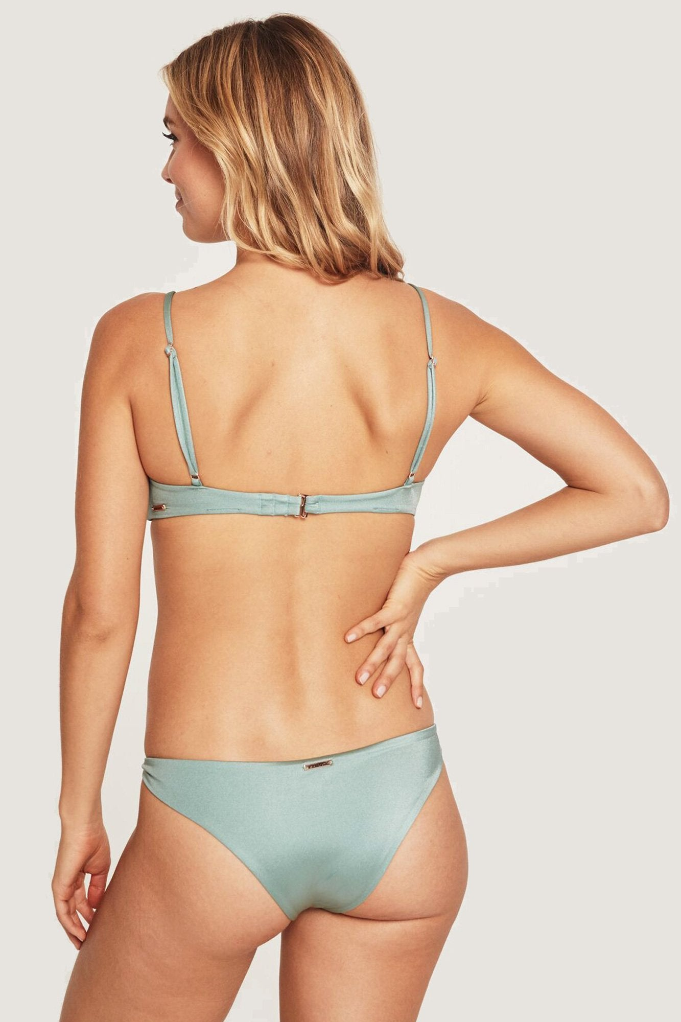 Back view of model wearing light, dusty green, low-rise bikini bottoms featuring knotted side detail and a cheeky cut.