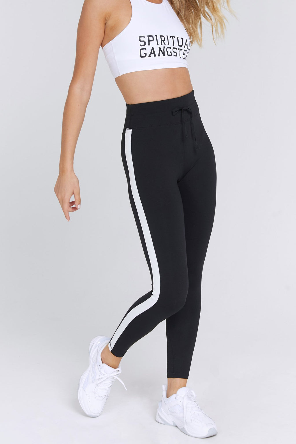 Model wears a pair of high waisted black spiritual gangster leggings. The sporty high waist legging has a vertical white, sparkly stripe down the side of the leg of the pant. It is a full length legging that comes with an exposed drawstring waistband.