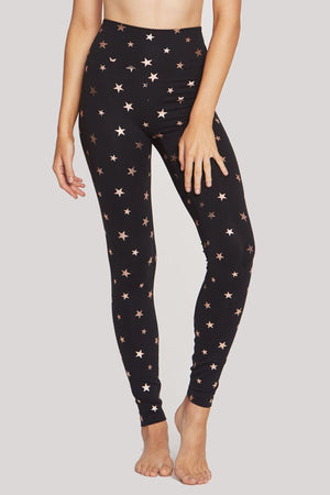 Model is wearing tight, black leggings that feature a high waist and rose gold foil stars printed all over.