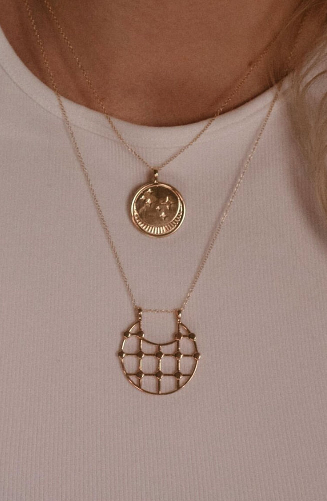 UNIKONCEPT Lifestyle boutique: image shows the Franz Necklace in gold onyx by Sarah Mulder. This necklace features a circular pendant engraved with a moon and star details as well as a small onyx stone. The pendant hangs from a delicate gold chain.