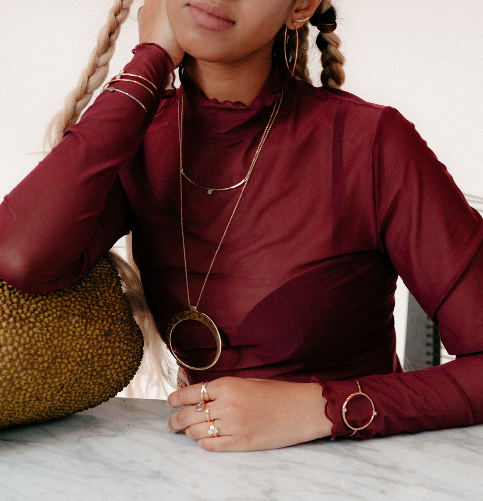 UNIKONCEPT Lifestyle boutique: image shows the Pulse Cuff in gold by Sarah Mulder. This gold cuff features a circle shaped face that is set with two moonstones at the top and bottom of the circle.