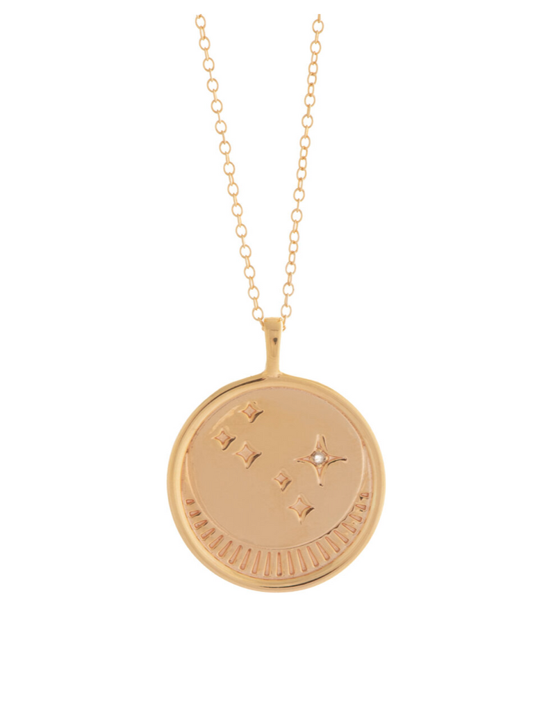 UNIKONCEPT Lifestyle boutique: image shows the Franz Necklace in gold rose quartz by Sarah Mulder. This necklace features a circular pendant engraved with a moon and star details as well as a small rose quartz stone. The pendant hangs from a delicate gold chain.