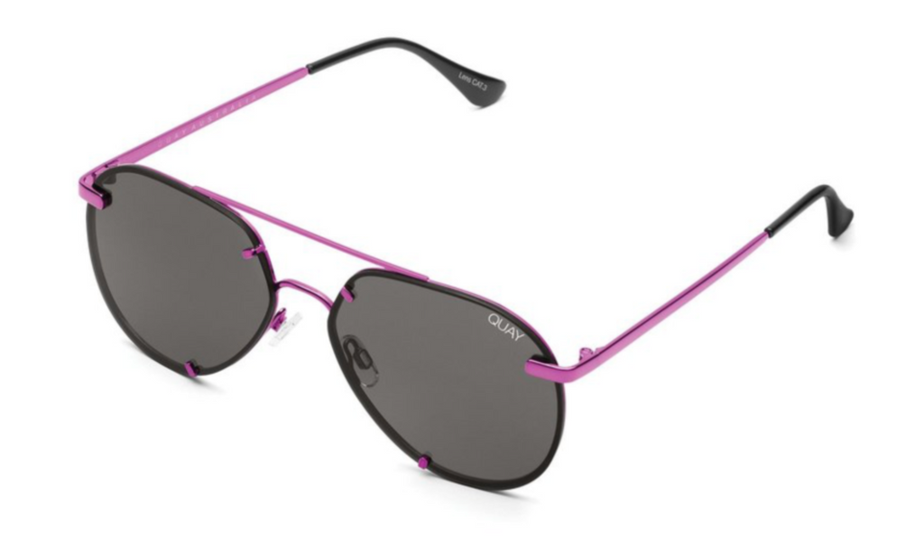 UNIKONCEPT: Lifestyle boutique; image shows a pair of quay sunglasses. the rebelle sunglasses are a geometric aviator style that is completely blacked out. It also features hot pink detailing around the rims of the glass and the bridge.