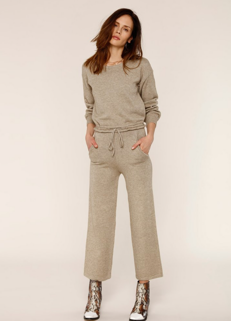 UNIKONCEPT:Lifestyle boutique; image shows a cream coloured lounge set by Heartloom. The Evie set features a crewneck and a pair of culottes. The crew neck is an olive green/cream colour and has a drawstring around the waist to tighten. The culottes are a shorter pant features an elastic waistband and a wide leg