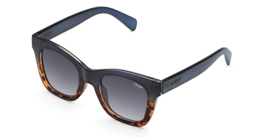 UNIKONCEPT: Lifestyle boutique; Image shows a pair of Quay sunglasses. The after hours are a large framed sunglass that features a navy blue top Frame and a tortoise shell bottom. The shade of glass is a dark grey almost black.