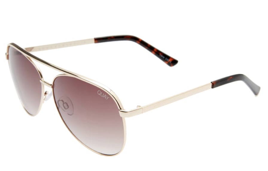 UNIKONCEPT: Lifestyle boutique; image shows a pair of quay sunglasses. The vivenne sunglasses are an oversized aviator styled sunglass, they are a taupe brown colour with gold rims and tortoise shell stems.