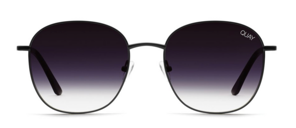 UNIKONCEPT: Lifestyle boutique; Image shows a rounded frame sunglass by Quay. The Jezabell sunglass in black fade has a thin. black, metal frame around the glass of the sunnies. The actual glass is a beautiful fade from black to transparent.