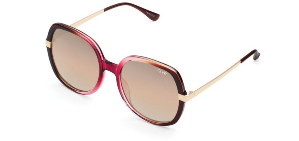 UNIKONCEPT: Lifestyle boutique; image shows a pair of quay sunglasses. The Gold dust sunglasses are a large, oversized circular/square like frames with small gold detailing around the outer eyes. The frame is a blend of pink and brown tones and the glass is a transparent brown colour.