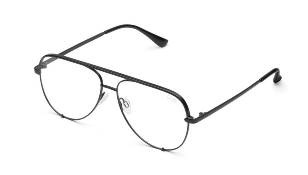 Image shows a pair of Quay Australia glasses. The high key blue light lens has transparent lenses with a blue light feature to them to eliminate the strain of light radiating from electronic devices. This pair comes in an aviator style with black and gold frames.