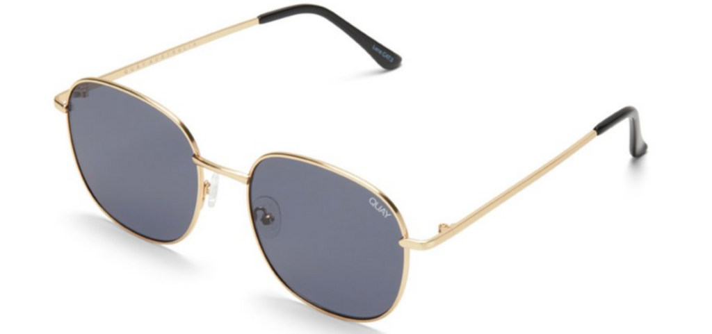 UNIKONCEPT: Lifestyle boutique; Image shows a rounded frame sunglass by Quay. The Jezabell sunglass in Gold smoke has a thin, gold, metal frame around the glass of the sunnies. The actual glass is a beautiful dark grey colour.