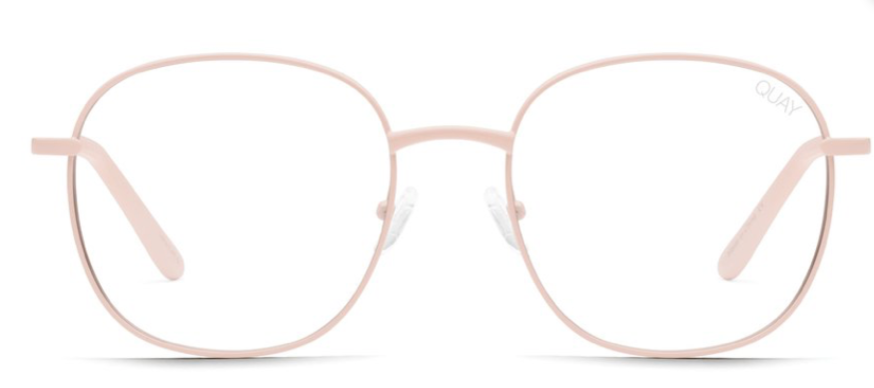 UNIKONCEPT: Lifestyle boutique; Image shows a rounded frame sunglass by Quay. The Jezabell sunglass in pink and clear has a thin, light pink metal frame around the glass of the sunnies. The actual glass is a blue light lens that is completely transparent and helps to protect against rays from technology.